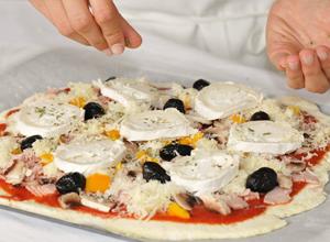 Saupoudrer l'origan sur la pizza sans gluten au chèvre